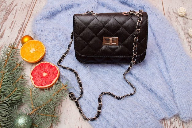 Fashion concept. black female bag on sweater, spruce branch and orange