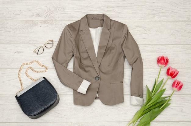 Fashion concept. classic jacket, handbag, sunglasses and pink tulips.