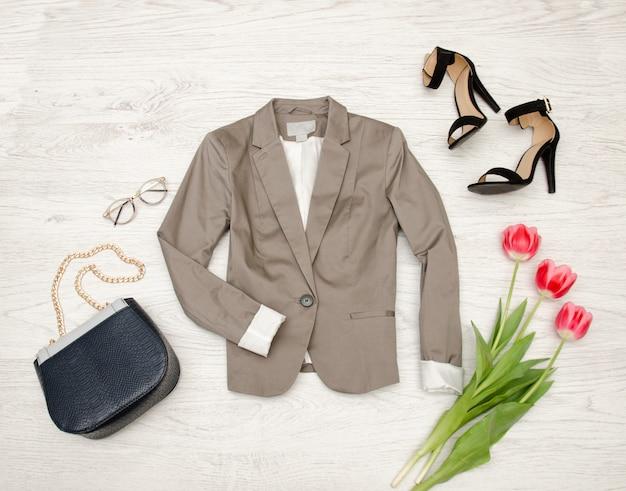 Fashion concept. gray jacket, handbag, sunglasses, shoes and pink tulips