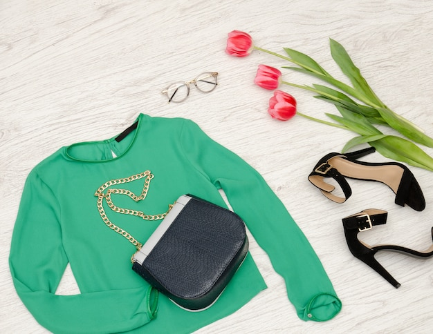 Fashion concept. green blouse, handbag, sunglasses, black shoes and pink tulips. top view