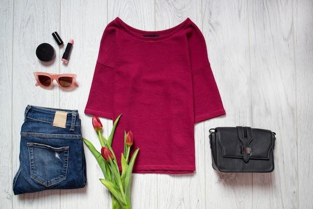 Концепция моды. бордовый топ, тюльпаны, синие джинсы, черная сумка, солнцезащитные очки, помада. весенний гардероб.