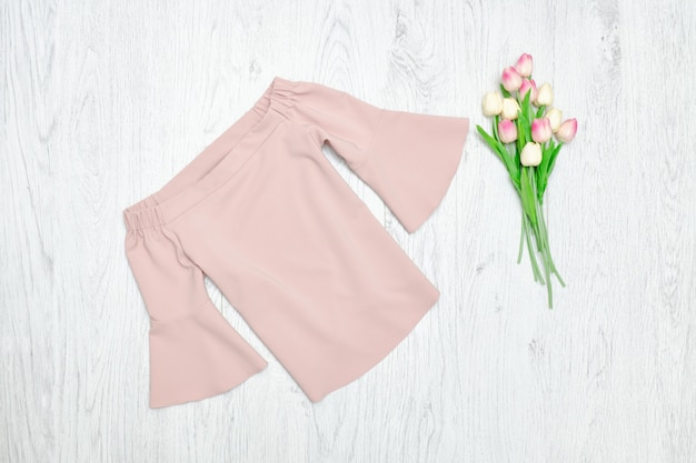 Fashion concept. pink blouse and pink tulips. wood background