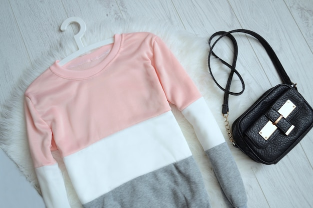 Fashion concept, pink and white sweater and handbag, top view