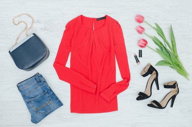 Fashion concept. red blouse, shoes,  handbag and pink tulips. top view