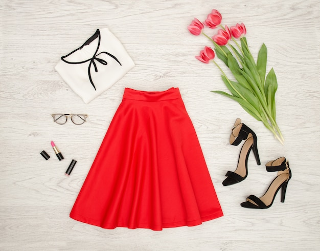 Fashion concept. red skirt, blouse, sunglasses, lipstick, black shoes and pink tulips, light wood background