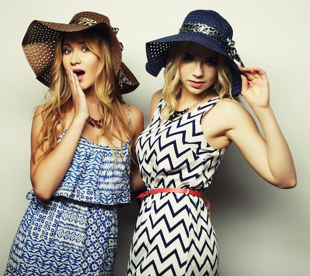 Концепция моды: две сексуальные молодые женщины в летнем модном платье и соломенных шляпах, студийный фон