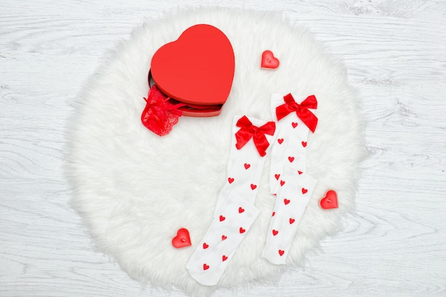 Fashion concept. white stockings and box in the shape of heart. white fur