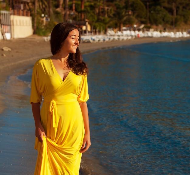 Концепция моды - женщина с длинным желтым платьем гуляет одна на пляже
