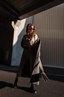 세련된 캐주얼 옷에 곱슬머리를 한 패션 멋진 예쁜 소녀는 긴 코트와 선글라스로 거리를 걷고 있습니다. 도시의 가을 여성 스타일