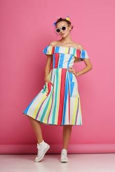 Мода прохладная женщина позирует на розовом. молодая хипстерская женщина с бигуди в волосах, солнцезащитные очки, белые кроссовки