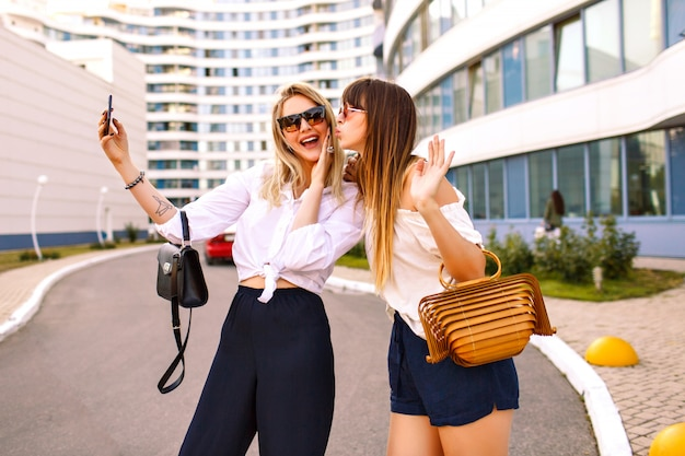 Fashion couple of beautiful trendy elegant woman wearing summer color matching classic feminine outfits, bags and sunglasses, making selfie end enjoying time together, traveling mood, summertime.