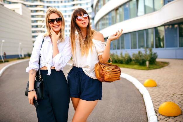 Coppia di moda di bella donna elegante alla moda che indossa il colore estivo che abbina abiti classici femminili, borse e occhiali da sole, in posa per strada, soleggiata giornata estiva primaverile, atmosfera di vacanza.