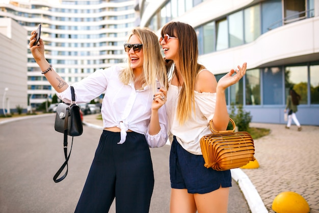 Модная пара красивой модной элегантной женщины, одетой в летний цвет, сочетающейся с классическими женственными нарядами, сумками и солнцезащитными очками, заставляет селфи наслаждаться временем вместе, путешествуя настроением, летом.