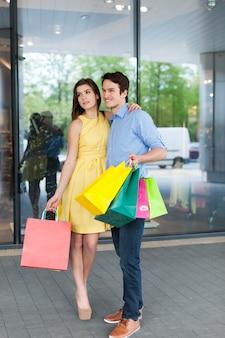 Пара моды позирует с хозяйственной сумкой