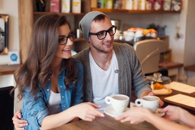 ウェイトレスからコーヒーを受け取るファッションカップル