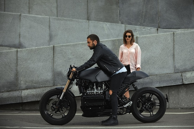 Fashion couple sitting on a motorcycle, stone wall on the background. young man and woman with modern motorcycle.