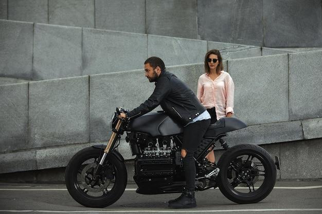 오토바이, 배경에 돌 벽에 앉아 패션 커플. 현대 오토바이와 젊은 남자와 여자.