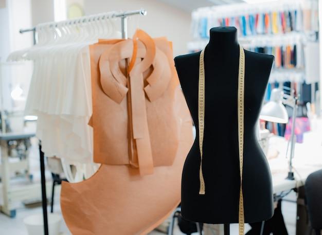 Концепция интерьера студии креативного дизайна моды с манекеном и стильной модной модной одеждой на вешалках, рабочее место шитья, ателье, швейная мастерская