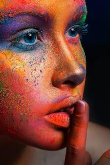 Модный культурный портрет модели красоты с красочным порошком составляет знак тишины шоу. красивая женщина с творческим составом всплеска. абстрактное красочное искусство макияж