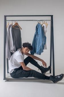 패션. 옷을 옷걸이 근처에 앉아 피곤해 보이는 곱슬 머리 젊은 남자