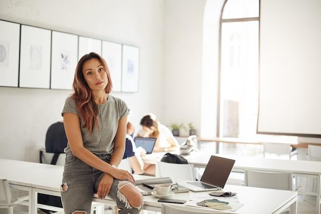 Apprendista di fashion design che studia in uno spazio di coworking o campus seduto sul tavolo con laptop e campioni tessili concetto di professioni alla moda.