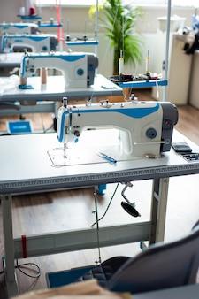Швейная машина для подвешивания одежды и различные сопутствующие товары на столе в студии дизайна одежды