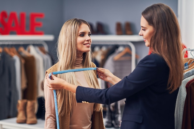Fashion designer assisting the customer in clothes boutique