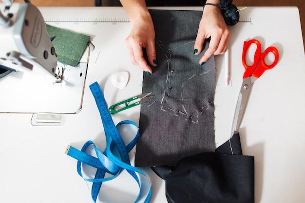 職場の机の上にドレスパターンを作成するファッションデザイナー