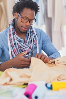 Fashion designer cutting clothes