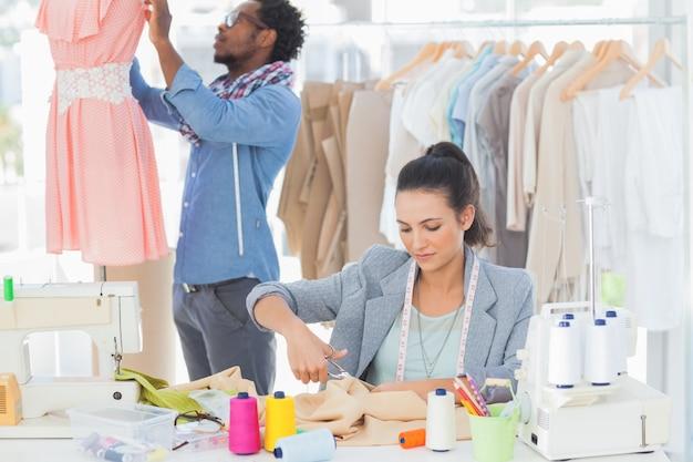 Fashion designer cutting textile at desk