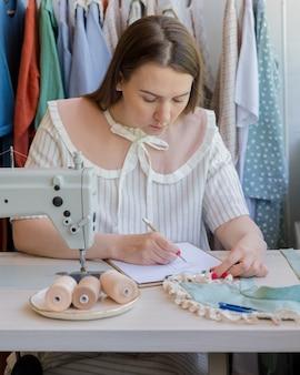 Модельер рисует эскиз одежды, сидя на своем рабочем месте со швейной машиной