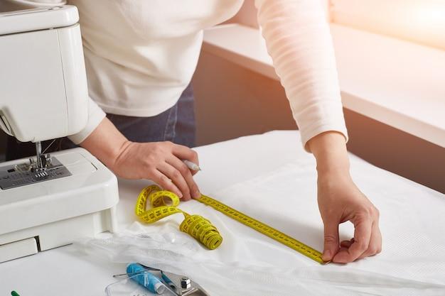 Fashion designer or dressmaker measures fabric. shallow depth of field.