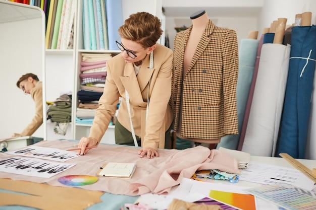 Модельер рассматривает за столом эскизы обновок и собирается шить платье в мастерской.