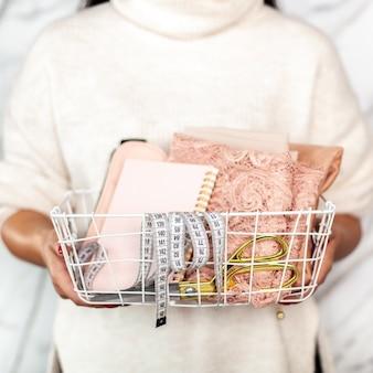 白いメッシュバスケットに折り畳まれたレース生地、仕立てはさみ、巻尺、メモ帳を持っているファッションデザイナーの手。レース生地からイブニングドレスを測定して縫うための仕立てツール。