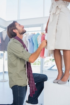 Fashion designer looking at model