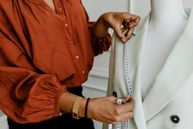 固定可能なマネキンのブレザーを測定するファッションデザイナー