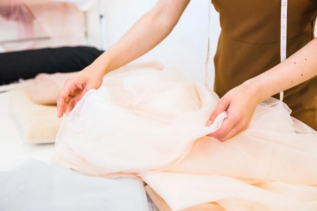 Fashion designer's hand working on textile in studio