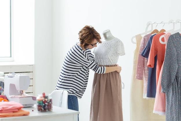 Модельер, швея и концепция малых предприятий - женщина-швея украшает