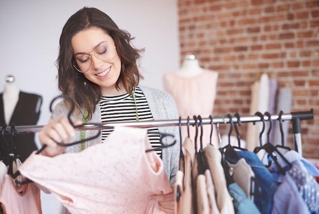 Модельер ищет наряды на вешалках для одежды