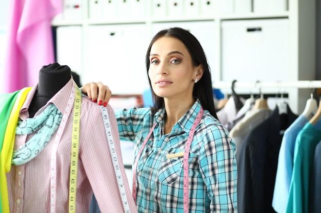 Модный дизайнер измеряет одежду на манекене