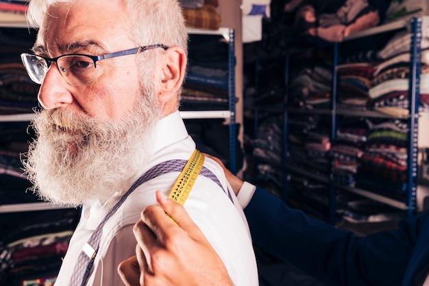 Fashion designer taking measurement of senior male customer