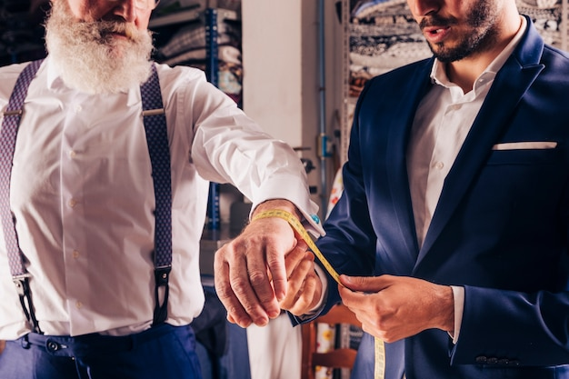 Fashion designer taking measurement of senior man's wrist with yellow measuring tape