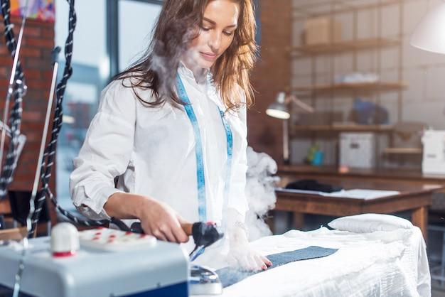 Fashion designer using steam iron to press cloth working