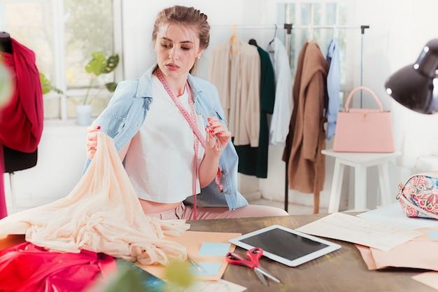 Fashion designer woman working in studio sitting on the desk