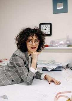 彼女のスタジオで働いているファッションデザイナーが新しいブライダルドレスコレクションを作成しています