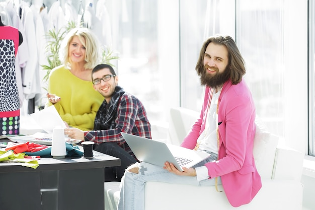 Fashion designer working on a laptop in a creative office