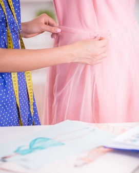 Fashion designer working in progress in tailor studio.