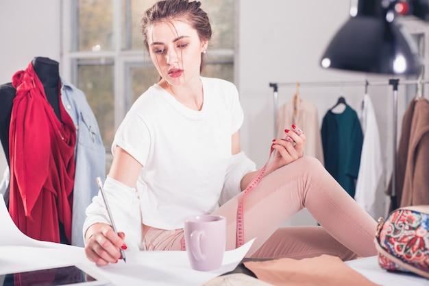 Stilista che lavora in studio seduto sulla scrivania