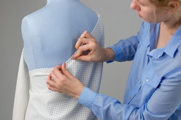彼女のワークショップで青いテーラーダミーと一緒に働いているファッションデザイナー。