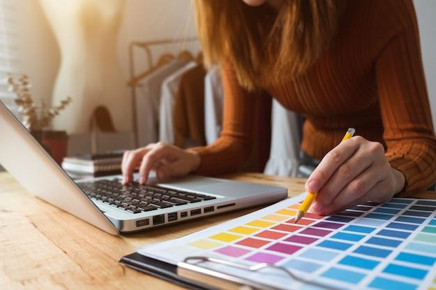 Модельер молодая азиатская женщина работает с ноутбуком